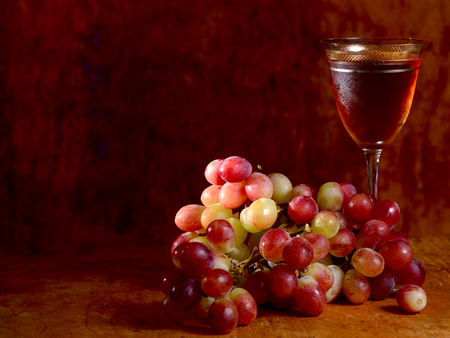 bunch of red grape and wine glass on a wooden tray