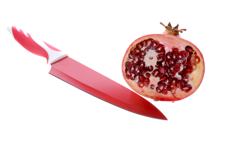 Ripe pomegranate and ceramic knife isolated on white background