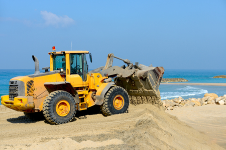 bulldozer working on a beach at sunny day