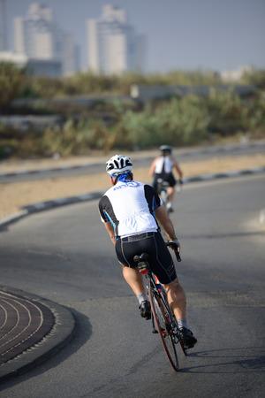 ASHKELON, ISRAEL- JUNE 09, 2017: Israeli adult men ride a bicycle along Ashkelon street.