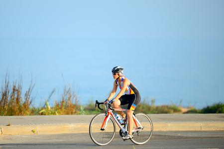 ASHELELON, ISRAEL-JUNE 09, 2017 : 이스라엘 노인 여성 Ashkelon 해변을 따라 자전거를 타고. 에디토리얼