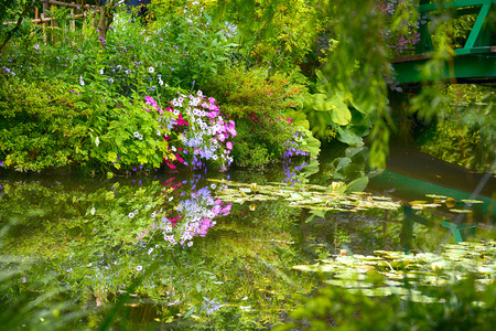Beautiful Claude Monets Garden of Giverny, Normandy, France in auturmn with the iconic green Japanese bridge reflecting in the water lilies pond Banco de Imagens