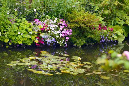 Beautiful Claude Monet's Garden of Giverny, Normandy, France in auturmn with the iconic green Japanese bridge reflecting in the water lilies pond