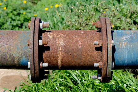 Closeup connecting pipe by weld to flange and bolt-nut. Pipeline for use in agriculture.
