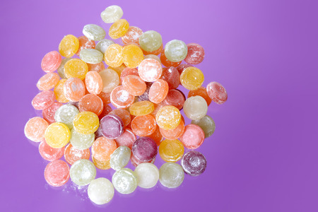Heap of colorful fruit hard sugar candies on a purple surface.