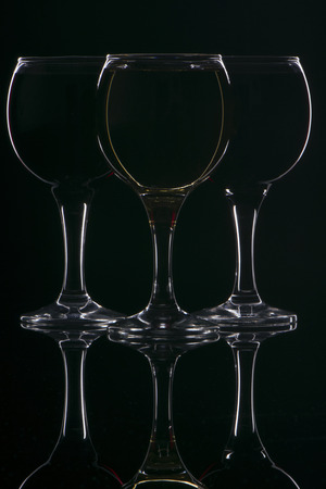unmarked: contours of three glasses with reflection in glass on a black background