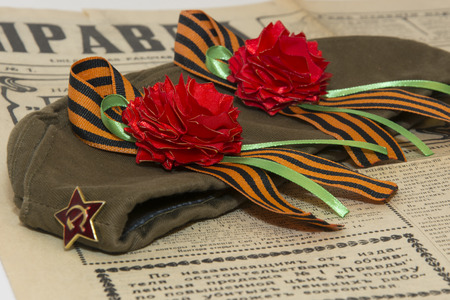 old newspaper: carnations with St.Georges Ribbons on a garrison cap and the old newspaper Stock Photo