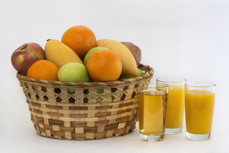 big basket with ripe fruit and glasses of juice photo