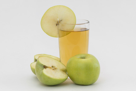 segmentar: vaso de jugo de manzana con las manzanas cortadas y un segmento de la manzana verde