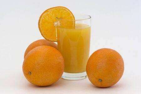 segmento: cuatro naranjas con un vaso de jugo y un segmento de naranja sobre un fondo blanco