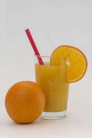 segmento: una naranja con un vaso de jugo y un segmento de naranja sobre un fondo blanco y un tubo Foto de archivo