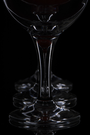 alcohol series: reflection of three glasses on a black background in black glass