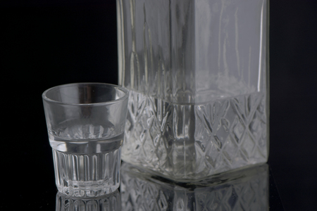 full shot: decanter with vodka and a full shot glass on a black background with reflection