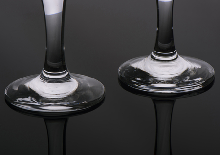 specular: specular reflection of a bottom of two legs of glasses on a gray background