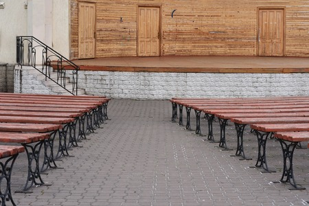 photograph of benches located in the future. benches are made of wood, they are brown. In the background of the stage and the stairs to the entrance to the stage