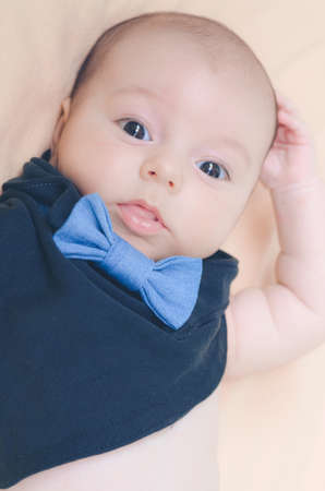 The baby in a black bib with a denim bow tie looks in surprise at the camera lens with his mouth slightly open .the background is blurred