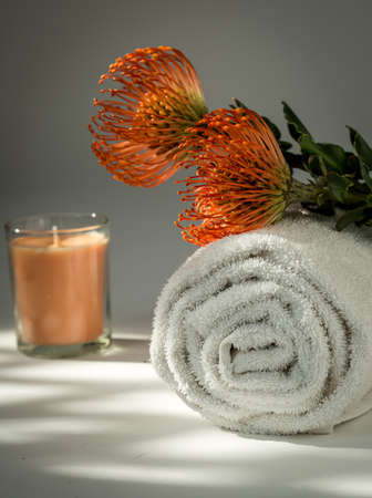 White Spa Towel ,Orange Protea flowers and Candle Banco de Imagens