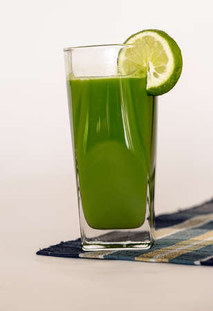 tall glass: Green Juice in a tall glass with Lime on Blue cloth
