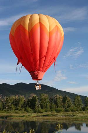 Globo aerostático naranja sobre el lago con montañas en fondo Foto de archivo - 39207301