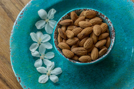 Almonds on Blue plate with White Flowers Stok Fotoğraf