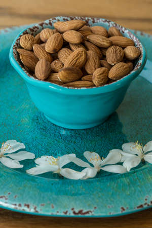 Almonds in Blue bowl with white flowers Stok Fotoğraf