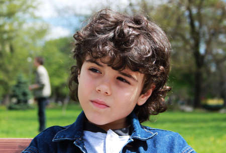 Portrait of a beautiful pensived child in the park photo