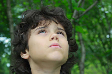 Close portrait of a beautiful boy who looks up to heaven with uplifted head up photo