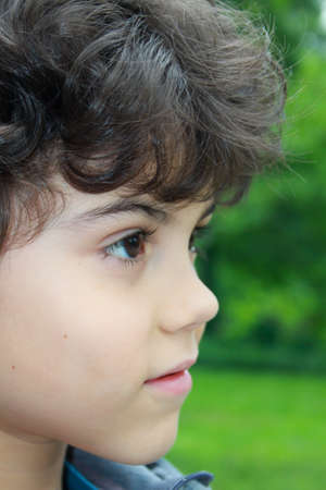 Closeup portrait of a beautiful boy with curly hair photo