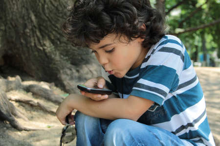 Beautiful curly child playing with cellphone sitting in the park photo