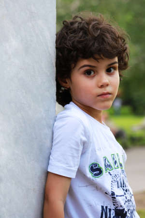 eyes hidden: Beautiful child with long curly hair stands to white marble wall Stock Photo
