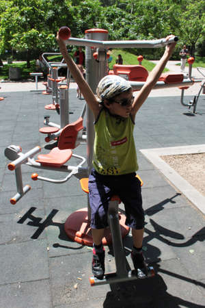 Curly boy with a headkerchief playing in a playground with fitness equipment Stock fotó