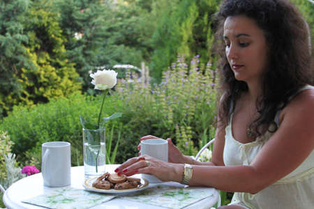 Young woman having a breacfast with cookies and tea in a summer garden, alone photo