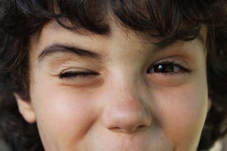 Close portrait of a little boy who winks photo
