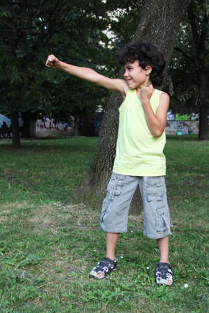 Little boy doing exercises in the green park photo