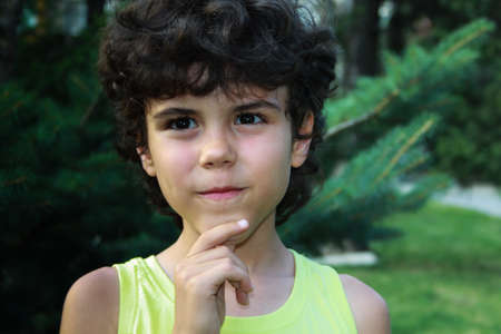 Portrait of a curly little boy in the summer park photo