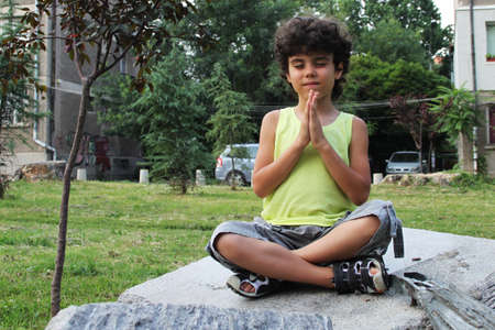 Little curly boy doing yoga in the park photo