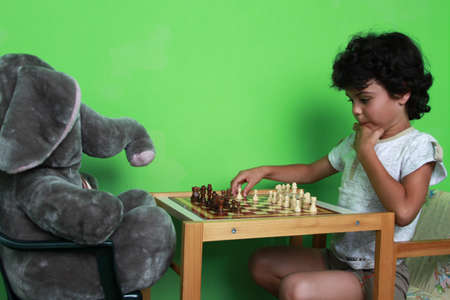 curly hair child: Happy little boy is playing chess with his toy elephant friend at home Stock Photo