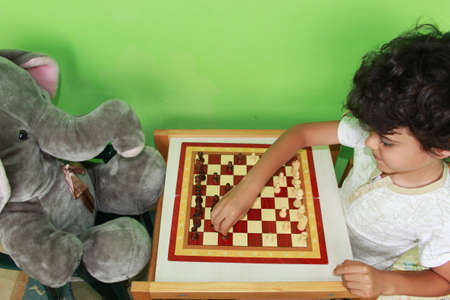 Happy little boy is playing chess with his toy elephant friend at home photo