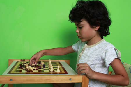 Little boy prepares for playing chess at home photo