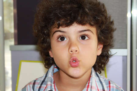 Curly little boy with cute expression photo