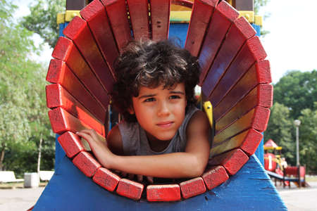 Curly boy is playing on the playground photo