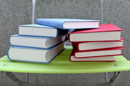Color books on a green chair, isolated photo