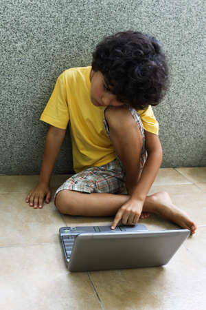 computer generation: A child sitting on the floor and working on  his laptop Stock Photo