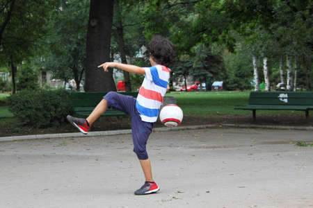Little boy is playing football in the park photo