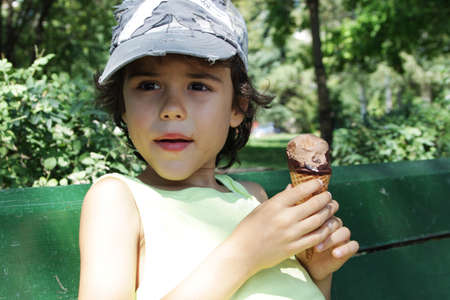 A charming boy eating an ice cream in the park photo