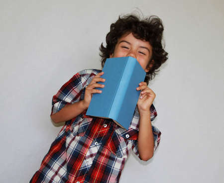 A playful boy with book in front of his face, isolated photo