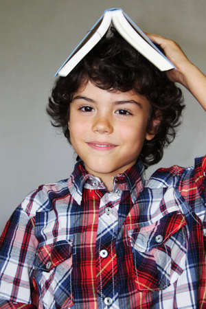A playful boy with a book on his head, isolated photo