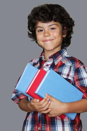 A charming boy with curly hair is holding books, isolated on grey background photo