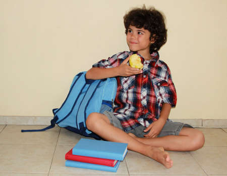 A beautiful smiling child with apple sitting on the floor surrounded with books and schoolbag photo