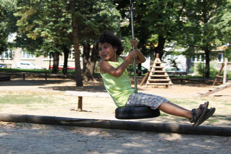 A happy boy on a swing of car tire in the park photo